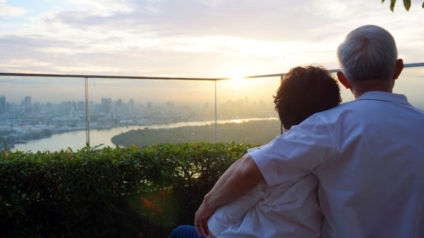 senior looking at sunrise together over city skyline and river