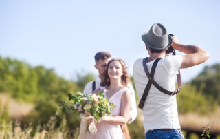 a wedding photographer takes pictures of the bride and groom in nature, the photographer in action